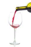Rotweinspritzen, das in ein Weinglas gegossen wird Lizenzfreies Stockbild
