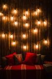 Rotwild gehen auf hölzernem Hintergrund des roten handgemachten Kissens im Innenraum voran Stockfoto