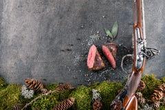 Rotwild- oder Wildbretsteak mit antikem Gewehr und Bestandteile mögen Seesalz, Kräuter und Pfeffer, Lebensmittelhintergrund für R stockfotos