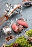 Rotwild- oder Wildbretsteak mit antikem Gewehr und Bestandteile mögen Seesalz und -pfeffer, Lebensmittelhintergrund für Restauran Stockfoto