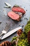 Rotwild- oder Wildbretsteak mit Bestandteilen mögen Seesalz, Kräuter und Pfeffer und Tischbesteck, Lebensmittelhintergrund für Re Stockfoto