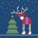 Rotwild verziert einen Weihnachtsbaum mit Stern in der Nacht Stockbild
