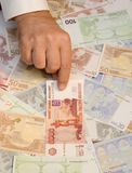 Rouble banknote with euro at the background. Man`s hand pointing to rouble banknote with euro at the background Royalty Free Stock Photography