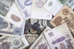 Rouble moderne de pièce de monnaie entouré par de vieux billets de banque de l'URSS Images stock