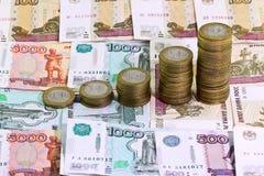 10 roubles de pièces de monnaie sur le fond d'argent de billet de banque Photographie stock libre de droits