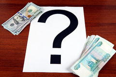 Roubles and Dollars. Russian Roubles and American Dollars with Question Mark on the Wooden Background Royalty Free Stock Photos