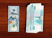 Roubles and Dollars. Russian Roubles and American Dollars on the Wooden Background Royalty Free Stock Image
