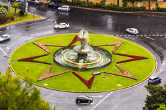 Roundabout in Malaga. A roundabout covered with grass and flowers, and cars driving. Capture taken in Malaga, Spain Stock Images