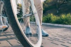 Roue d'une bicyclette et pieds femelles dans des espadrilles Images stock