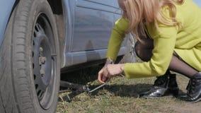 Roue de changement de essai de femme blonde séduisante sur une voiture sur la route rurale 4K banque de vidéos