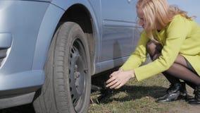 Roue de changement de essai de femme blonde séduisante sur une voiture sur la route rurale Mouvement lent banque de vidéos