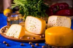 Roue de fromage sur un conseil en bois Fond brouill? image stock