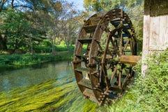 Roue de moulin à eau sur la rivière le jour ensoleillé Images stock