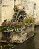 Roue de moulin avec des fleurs, France Image stock