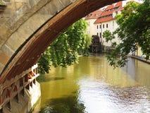 Roue de moulin historique à la rivière de Vltava vue sous le pont photos stock