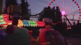 Roue de tour et de ferris de parc d'attractions avec la lumière colorée de clignotant la nuit banque de vidéos