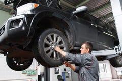Roue de voiture diagnosting de mécanicien avec le tournevis images stock