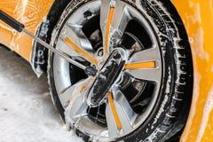 Roue de voiture jaune lavée dans la lave-auto de service d'individu, disque en aluminium de jante de nettoyage de brosse couvert  images libres de droits