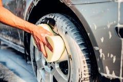Roue de voiture masculine de frottage de main avec la mousse, lave-auto photographie stock