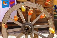 Roue en bois décorée de petits pots de poterie de terre sur l'exhibi Photo libre de droits