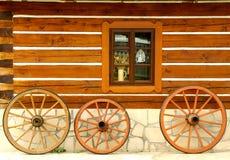 Roues en bois au mur de maison Image libre de droits