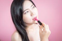Rouge à lèvres asiatique de femme de longs cheveux jeune beau, d'isolement au-dessus du fond rose maquillage, soins de la peau, c Photo libre de droits
