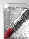 Rouge à lèvres rouge à l'intérieur d'un verre de l'eau de scintillement photographie stock