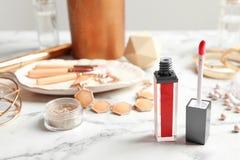 Rouge à lèvres liquide avec l'applicateur et les accessoires sur la table photographie stock
