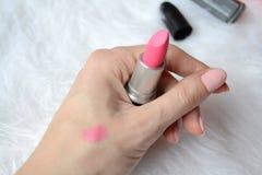 Rouge à lèvres rose dans une main femelle, trace de rouge à lèvres sur son poignet dans la perspective de la fourrure blanche photos libres de droits