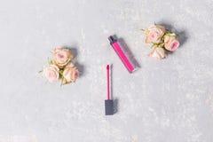 Rouge à lèvres rose, lustre de lèvre, ouvert, avec les roses d'arbuste roses sensibles sur les bords sur le fond gris blanc, plan photos libres de droits