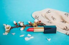 Rouge à lèvres rouge Brin avec des fleurs d'amande Fond pour une carte d'invitation ou une félicitation Photo stock