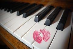 Rouge à lèvres sur un piano Images stock