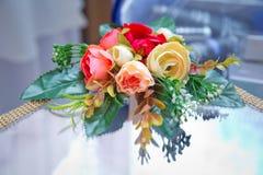 Rouge artificiel, bouquet de rose de jaune Fond décoratif de fleurs artificielles Image stock