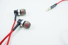 Rouge d'écouteur et de cric mis dessus un fond blanc photo stock