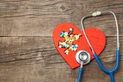 Rouge de puzzle de coeur et pilules et stéthoscope de couleur sur un fond en bois de fond Traitement de concept des pilules de ma photo libre de droits
