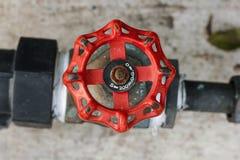 Rouge de valve coupée de l'eau sur le plancher photos stock
