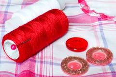Rouge et fil et boutons de blanc sur un tissu à carreaux Accessoires de couture Photos libres de droits