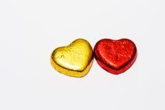 Rouge et isolat de bonbons au chocolat à coeur d'or sur le fond blanc Photos libres de droits