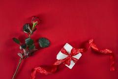 On rouge foncé s'est levé avec le ruban et le boîte-cadeau rouges sur le fond rouge Photos stock
