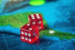 Rouge jouant des os sur la carte du monde des jeux de société faits main de champ Images stock