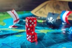 Rouge jouant des os sur la carte du monde des jeux de société faits main de champ avec un bateau de pirate Images libres de droits