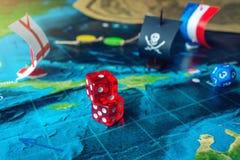 Rouge jouant des os sur la carte du monde des jeux de société faits main de champ avec un bateau de pirate Image stock