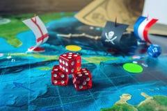 Rouge jouant des os sur la carte du monde des jeux de société faits main de champ avec un bateau de pirate Photographie stock libre de droits