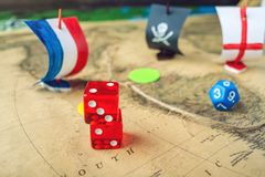 Rouge jouant des os sur la carte du monde des jeux de société faits main de champ avec un bateau de pirate Photo libre de droits