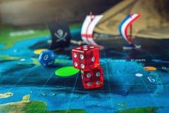 Rouge jouant des os sur la carte du monde des jeux de société faits main de champ avec un bateau de pirate Images stock