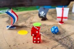 Rouge jouant des os sur la carte du monde des jeux de société faits main de champ avec un bateau de pirate Photographie stock