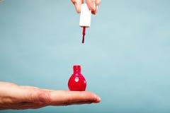 Rouge manucure de pédicurie vernis à ongles sur la paume femelle Photographie stock