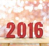 Rouge nombre en bois de 2016 ans sur le dessus de table en bois avec la goupille de scintillement Photographie stock libre de droits