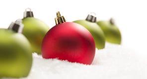 Rouge unique parmi les ornements verts de Noël sur la neige Images stock