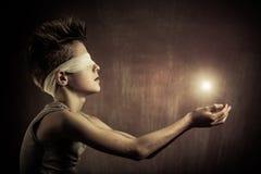 Rougeoyer léger au-dessus des mains ouvertes d'un garçon aveugle Photos stock